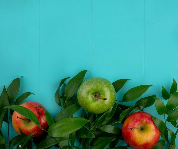 Bovenaanzicht van groene en rode appels met bladeren op een lichtblauw oppervlak