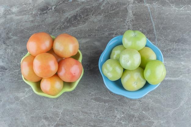 Bovenaanzicht van groene en rode tomaten op grijze achtergrond.