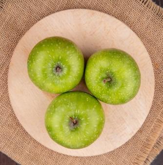 Bovenaanzicht van groene en verse appels op een houten keuken bord op zak doek oppervlak