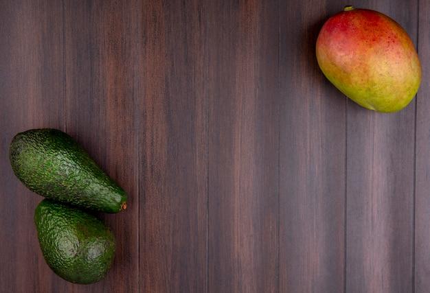 Bovenaanzicht van groene en verse avocado en mango op een houten oppervlak