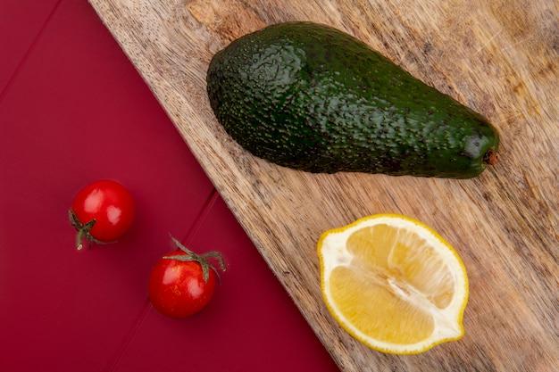 Bovenaanzicht van groene en verse avocado op een houten keuken bord met schijfje citroen en cherry tomaten op rode ondergrond