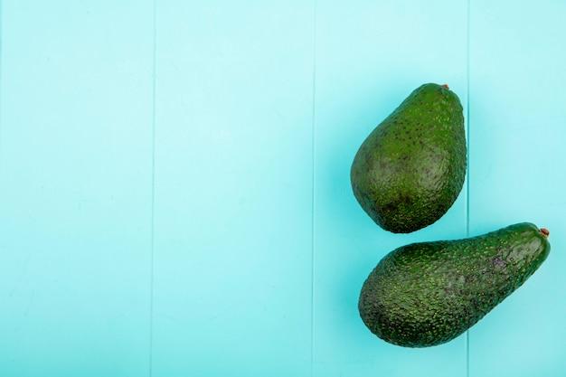 Bovenaanzicht van groene en verse avocado's op blauwe ondergrond