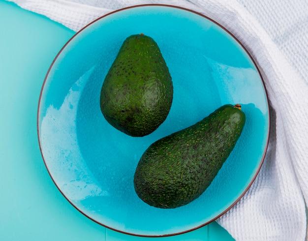 Bovenaanzicht van groene en verse avocado's op een bord op een wit tafellaken op blauwe ondergrond