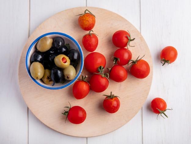 Bovenaanzicht van groene en zwarte olijven in kom en tomaten op snijplank en houten oppervlak