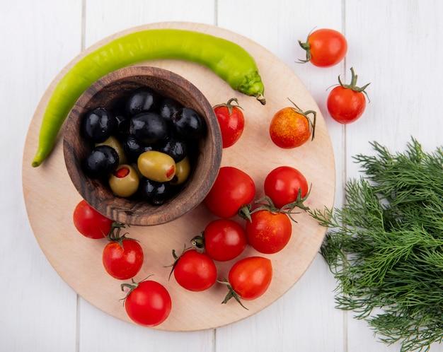 Bovenaanzicht van groene en zwarte olijven in kom en tomaten peper op snijplank met dille op houten oppervlak