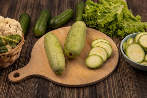 Bovenaanzicht van groene gevilde courgettes geïsoleerd op een houten keukenbord met bloemkool op een emmer met komkommers en sla geïsoleerd op een houten achtergrond
