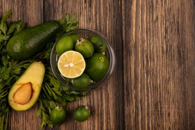 Bovenaanzicht van groene gevilde feijoas met limoenen op een glazen kom met avocado feijoas en peterselie geïsoleerd op een houten oppervlak met kopie ruimte