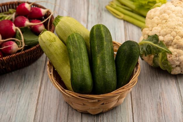 Bovenaanzicht van groene groenten zoals komkommers en courgettes op een emmer met radijs op een emmer met bloemkool en selderij geïsoleerd op een grijze houten muur