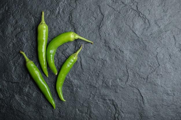 Bovenaanzicht van groene hete pepers op zwarte achtergrond