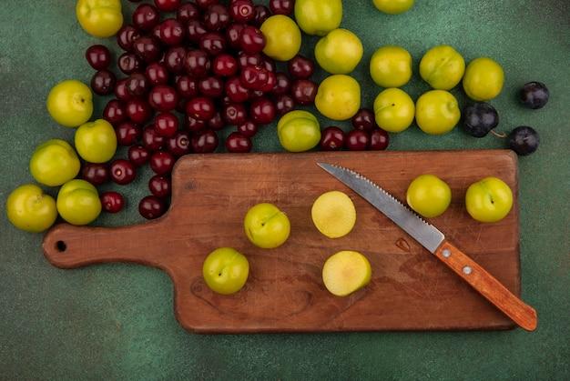Bovenaanzicht van groene kersenpruim op een houten keukenbord met mes met rode kersen op een groene achtergrond