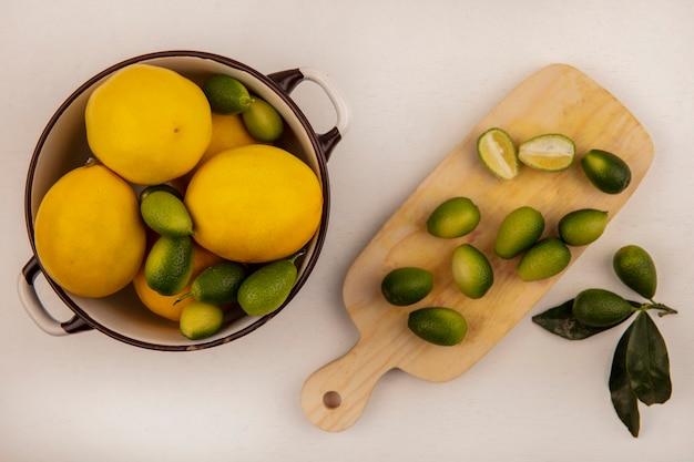 Bovenaanzicht van groene kinkans op een kom met citroenen met halve kinkans geïsoleerd op een houten keukenbord op een witte muur