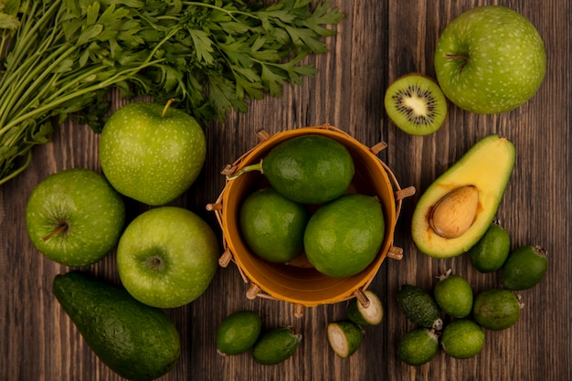 Bovenaanzicht van groene limoenen op een emmer met appels, kiwi, feijoas, avocado's en peterselie geïsoleerd op een houten muur
