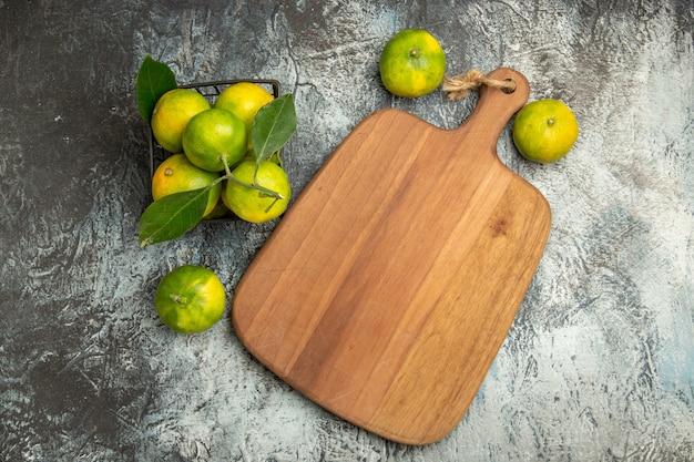 Bovenaanzicht van groene mandarijnen met bladeren binnen en buiten de mand en snijplank op grijze tafel