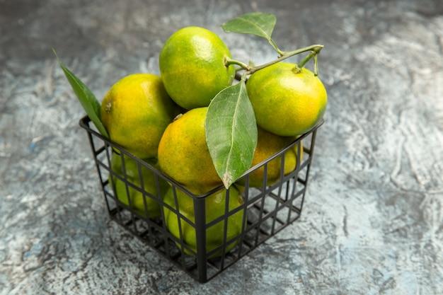 Bovenaanzicht van groene mandarijnen met bladeren in een mand op grijze achtergrond