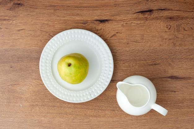 Bovenaanzicht van groene peer op een witte keramische plaat en lege melkkan op houten tafel.
