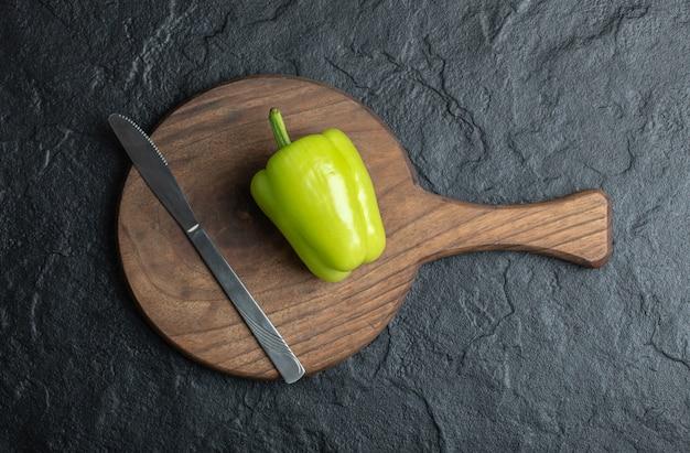 Bovenaanzicht van groene peper op houten snijplank met mes.