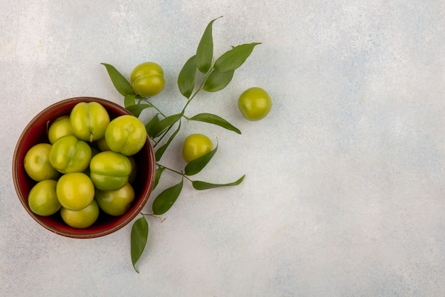 Bovenaanzicht van groene pruimen in kom met bladeren op witte achtergrond met kopie ruimte