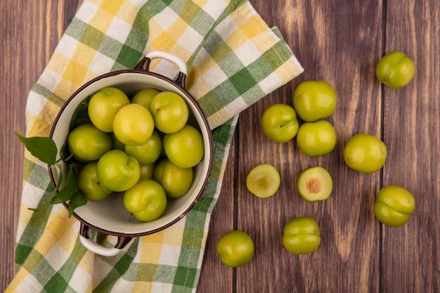 Bovenaanzicht van groene pruimen in kom op geruite doek en op houten achtergrond