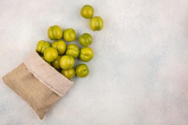 Bovenaanzicht van groene pruimen morsen uit zak op witte achtergrond met kopie ruimte
