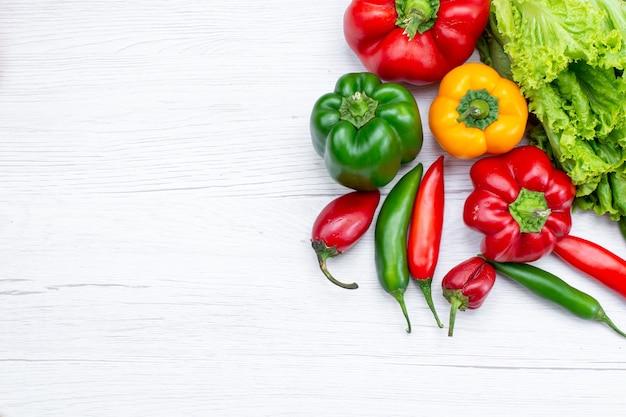 Bovenaanzicht van groene salade samen met paprika en pittige paprika op wit bureau, plantaardige voedselmaaltijd