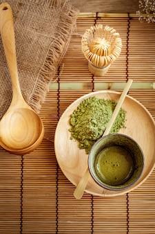 Bovenaanzicht van groene thee matcha in een kom op houten oppervlak