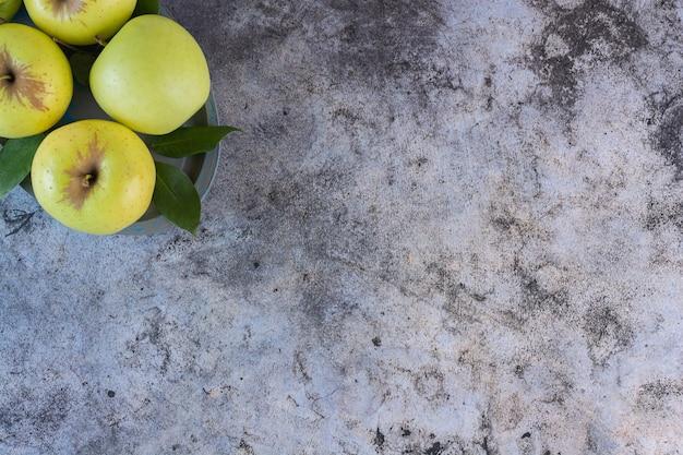 Bovenaanzicht van groene verse appels met bladeren op grijs.