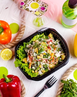 Bovenaanzicht van groente salade met champignons paprika wortel dille en roomsaus in een levering doos