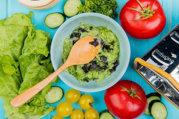 Bovenaanzicht van groente salade met sla komkommer tomaten koriander en rasp met houten lepel op blauw