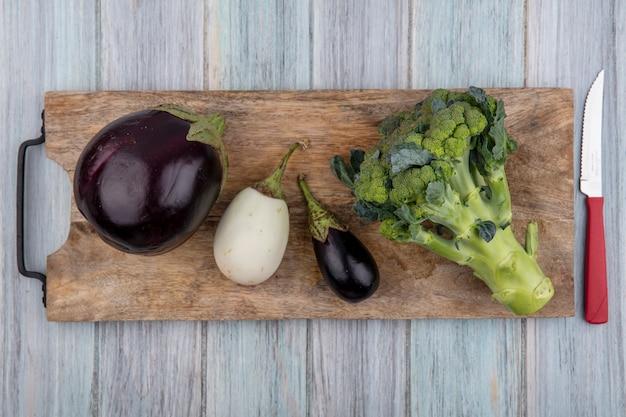 Bovenaanzicht van groenten als aubergines en broccoli op snijplank met mes op houten achtergrond