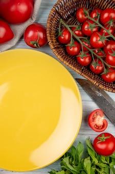 Bovenaanzicht van groenten als bladeren van de tomaat de groene munt met mes en lege plaat op houten oppervlak