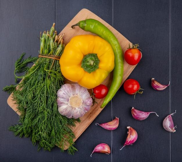Bovenaanzicht van groenten als bos van dille bol van knoflook peper tomaat op snijplank met knoflookteentjes op zwarte ondergrond