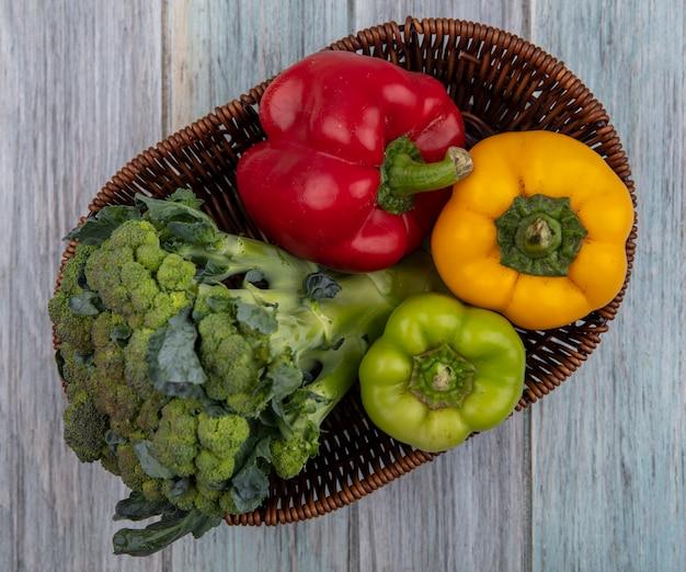 Bovenaanzicht van groenten als broccoli en paprika in mand op houten achtergrond