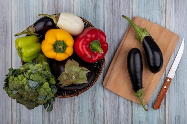 Bovenaanzicht van groenten als broccoli peper en aubergine in mand en aubergines op snijplank met mes op houten achtergrond