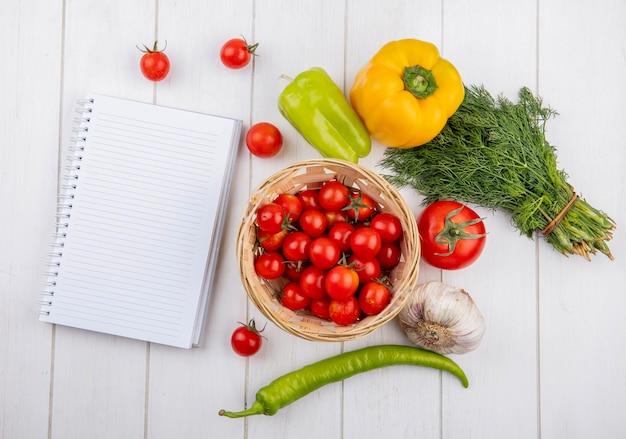 Bovenaanzicht van groenten als knoflook dille van de tomatenpeper met blocnote op houten oppervlakte