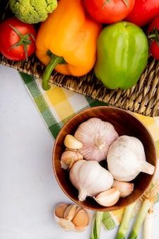 Bovenaanzicht van groenten als knoflook, paprika en tomaten op rieten mand