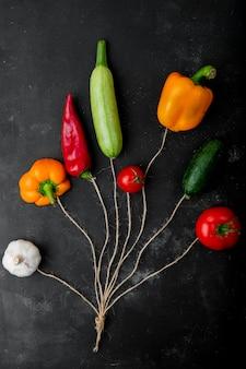 Bovenaanzicht van groenten als knoflook, peper, courgette, tomaat en komkommer op zwarte ondergrond