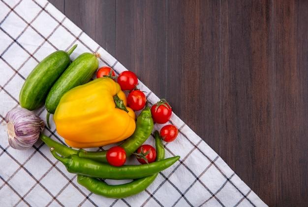 Bovenaanzicht van groenten als knoflook peper komkommer en tomaat op geruite doek en houten oppervlak