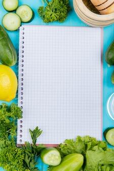 Bovenaanzicht van groenten als komkommer koriander sla met citroen en knoflook crusher en notitieblok op blauw oppervlak met kopie ruimte