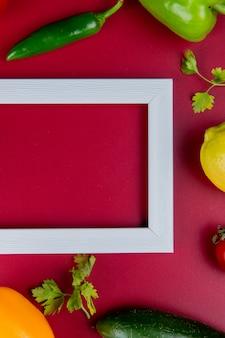 Bovenaanzicht van groenten als komkommer peper koriander met citroen en frame op bordo oppervlak met kopie ruimte