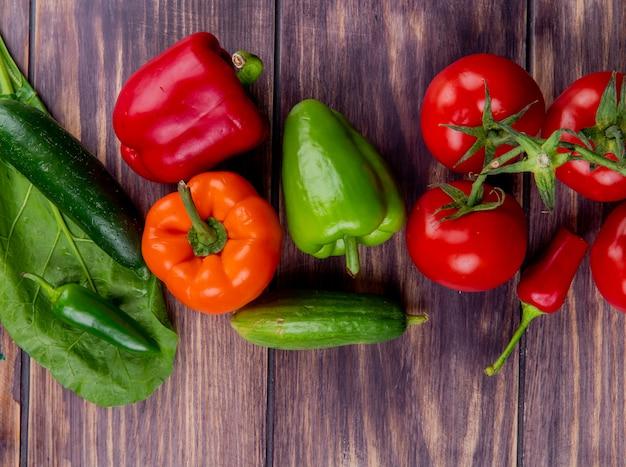 Bovenaanzicht van groenten als komkommer tomatenpeper op hout versierd met verlof