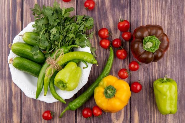 Bovenaanzicht van groenten als komkommer van peper koriander in plaat met tomaten op houten oppervlak
