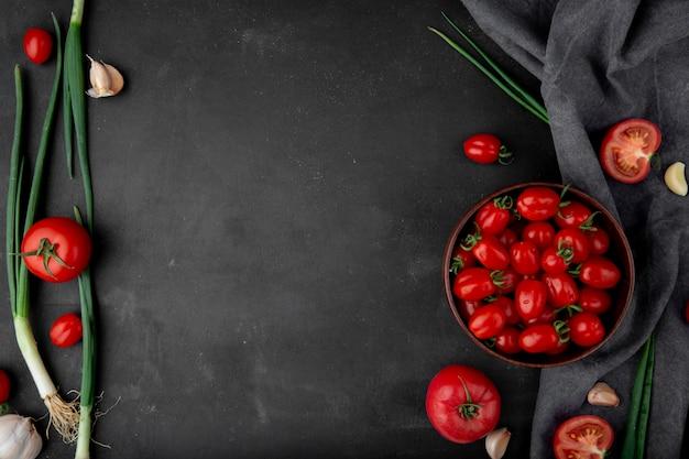 Bovenaanzicht van groenten als lente-uitjes tomaten en knoflook op zwarte ondergrond