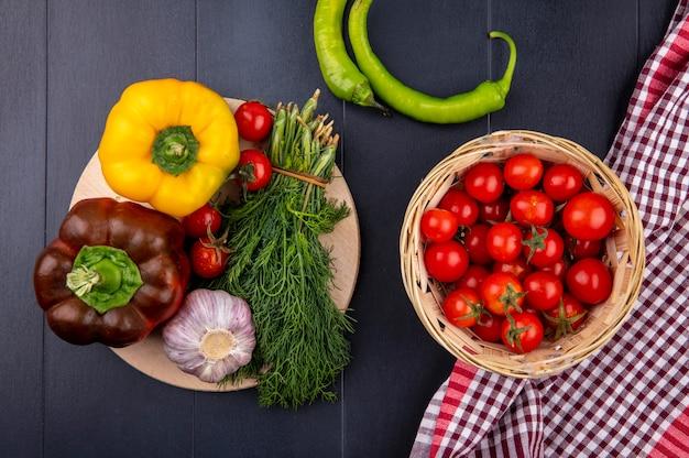 Bovenaanzicht van groenten als mandje tomaat op geruite doek met peper tomaten knoflook bosje van dille op snijplank op zwarte ondergrond