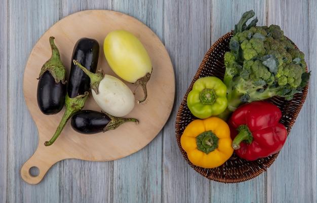 Bovenaanzicht van groenten als paprika en broccoli in mand met aubergines op snijplank op houten achtergrond