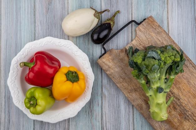 Bovenaanzicht van groenten als paprika in kom en broccoli op snijplank met aubergines op houten achtergrond