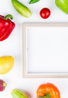 Bovenaanzicht van groenten als paprika komkommer radijs tomaat met frame op witte ondergrond met kopie ruimte