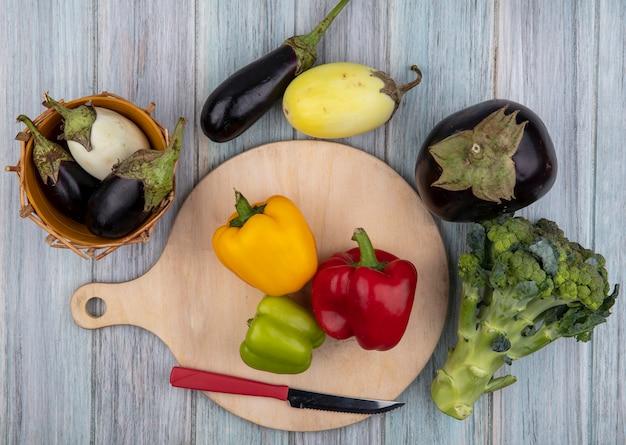 Bovenaanzicht van groenten als paprika met mes op snijplank en aubergines met broccoli op houten achtergrond