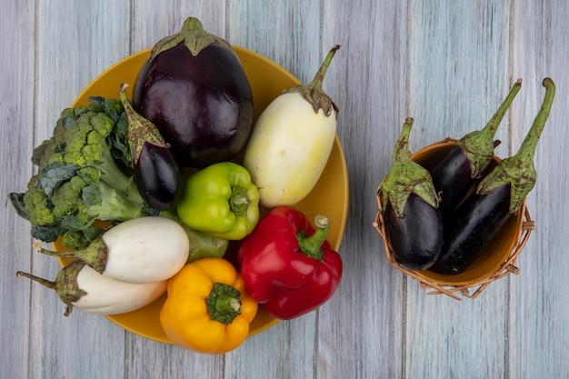 Bovenaanzicht van groenten als peper, broccoli en aubergine in plaat en aubergines in mand op houten achtergrond