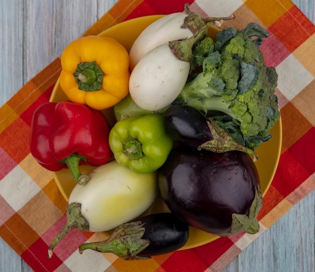 Bovenaanzicht van groenten als peper, broccoli en aubergine in plaat op geruite doek op houten achtergrond
