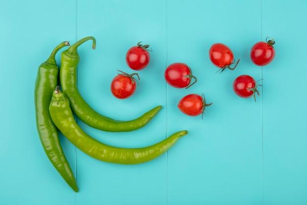 Bovenaanzicht van groenten als peper en tomaat op blauwe ondergrond